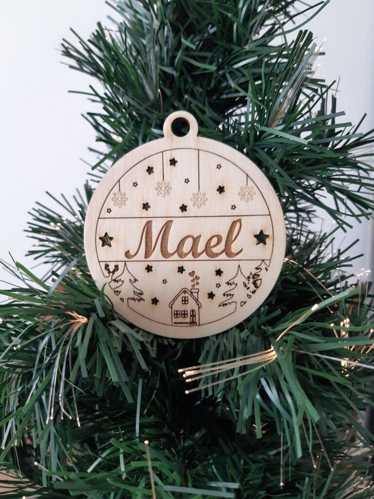 Boule de noel prénom personnalisée en bois avec chalet et flocon dans un sapin Mael