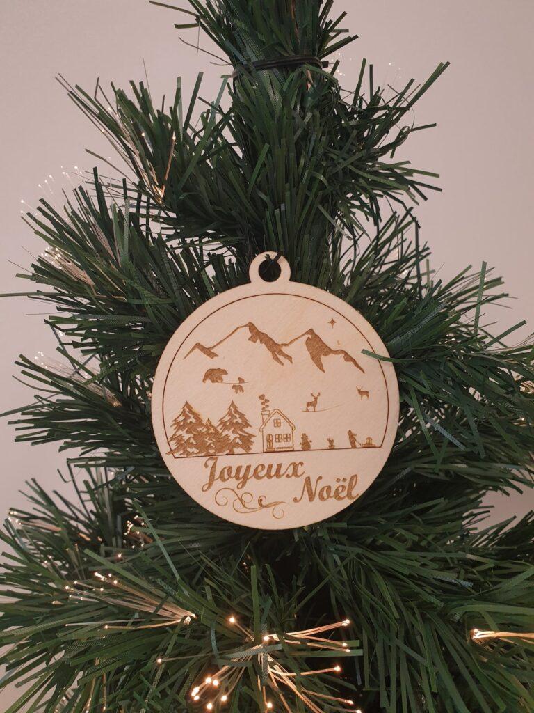 Boule de noel en bois gravé d'un paysage de montagne avec animaux et chalet