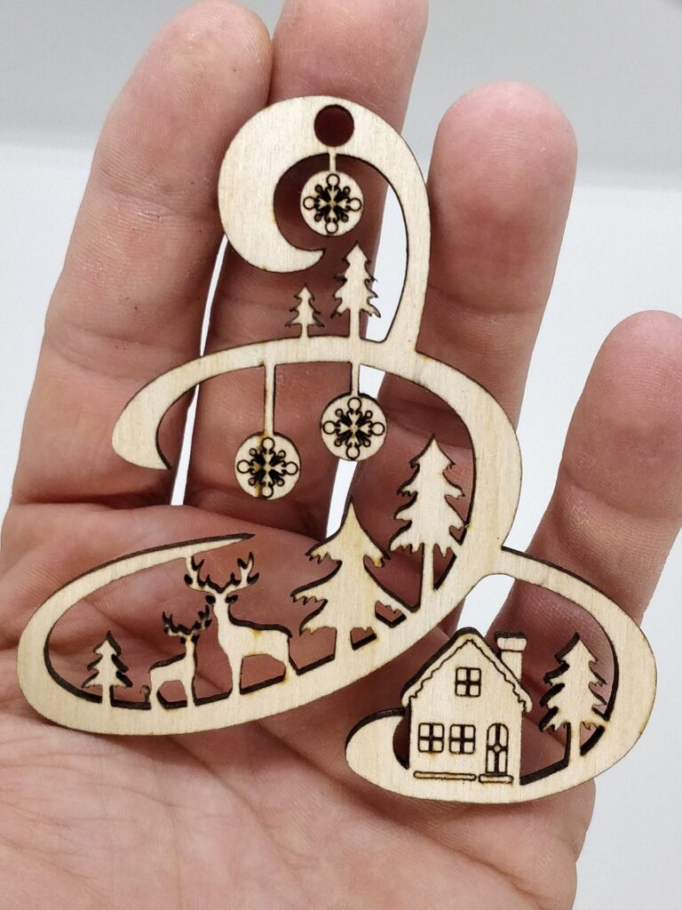 Boule de noël en bois gravé originale pour décorer votre sapin tenue dans la main