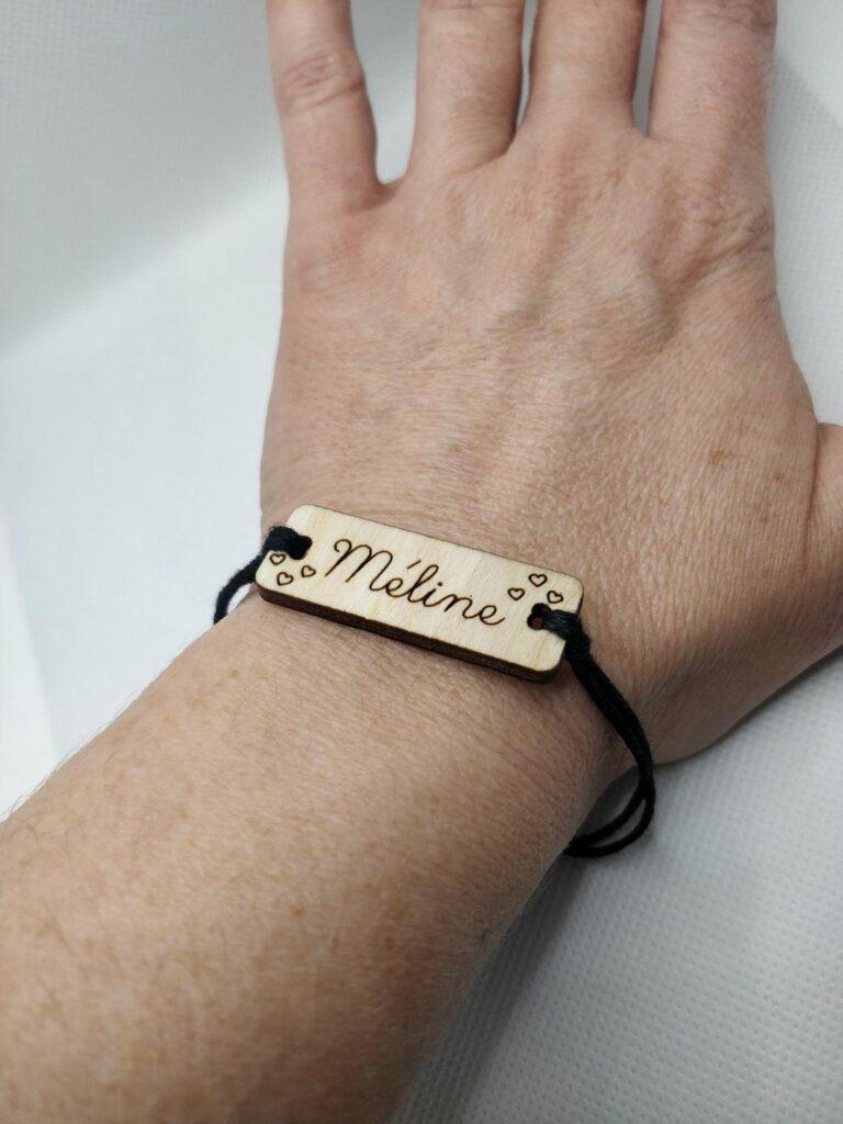 Bracelet personnalisé en bois gravé et coton ciré réglable avec prénom et cœur fin au poignet d'un adulte